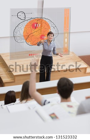 Teacher in front of futuristic interface with brain on it pointing student - stock photo