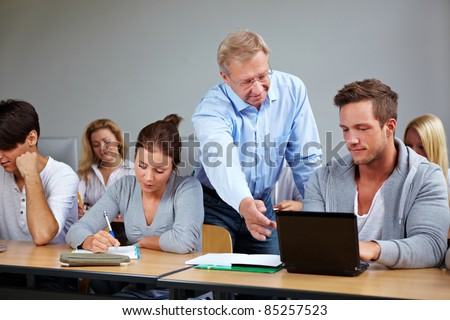 Teacher in university talking to his students - stock photo