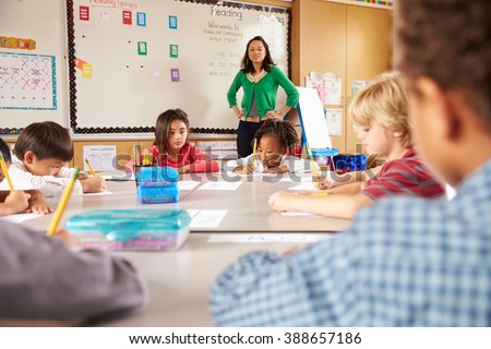 Teacher instructing elementary school kids in classroom - stock photo