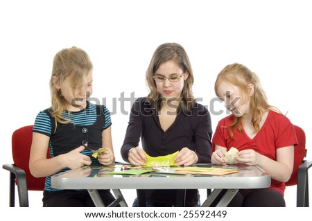 teacher is showing two little girls how to diy on white - stock photo