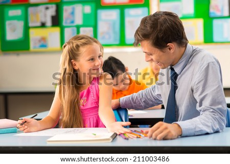 Teacher looking at drawing of his pupil at lesson - stock photo