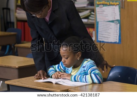 Teacher looking over students shoulder, as she works on her workbook in the class room - stock photo