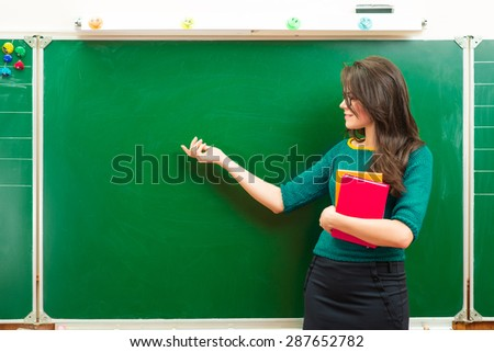 Teacher near blackboard in the classroom,