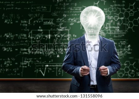 Teacher or college professor with a light bulb head in front of a chalkboard with complex math problems. - stock photo