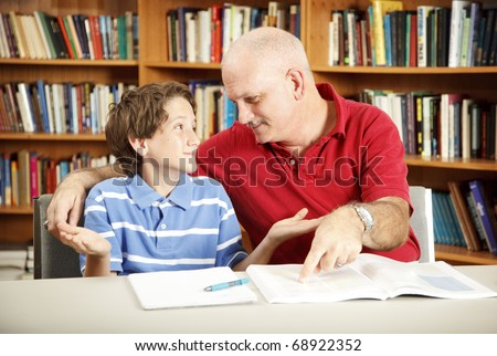 Teacher or parent working with a young boy who has learning disabilities.