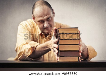 Teacher putting in order a stack of books - stock photo