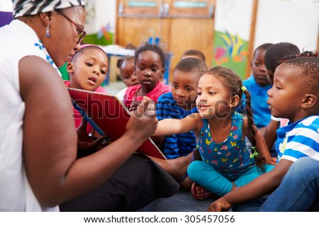 Teacher reading a book with a class of preschool children - stock photo