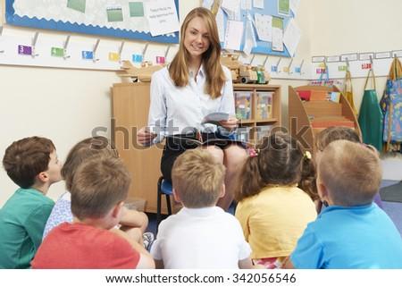 Teacher Reading Book To Elementary School Class - stock photo