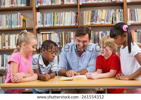 Teacher reading book to pupils at library at elementary school - stock photo