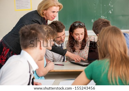 Teacher showing a laptop to a group of her students in a classroom - stock photo