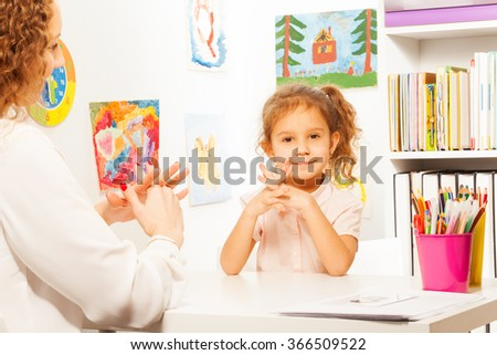 Teacher showing finger exercises to pupil at table - stock photo