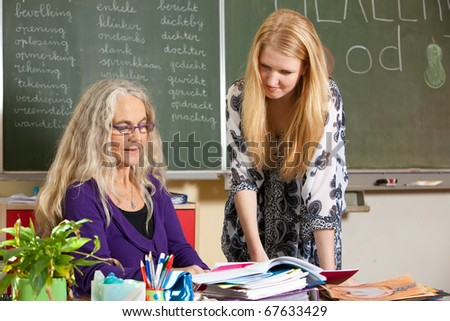 Teacher showing something to her student at her desk - stock photo