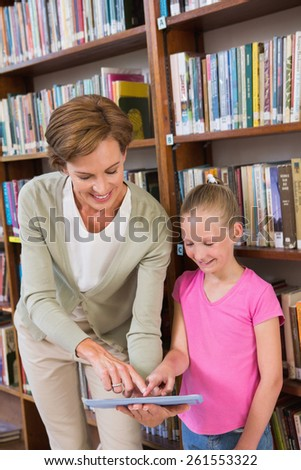 Teacher showing tablet to pupil at library at elementary school - stock photo