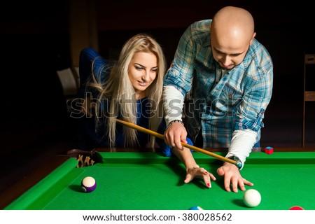 Teacher shows a girl how to play pool billiard. Billiard sport concept. American pool billiard. Pool billiard game. - stock photo