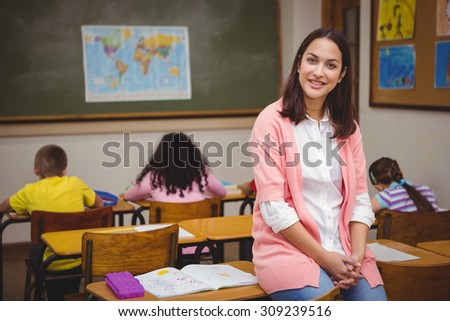 Teacher sitting behind her students at the elementary school - stock photo