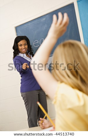 Teacher smiling and pointing to student with hand raised. Vertically framed shot. - stock photo