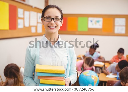 Teacher smiling at camera in classroom at the elementary school - stock photo