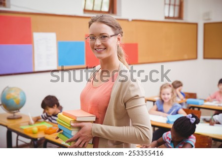 Teacher smiling at camera while holding stack of notebooks at the elementary school - stock photo