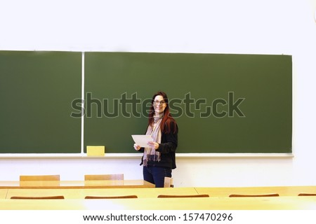 Teacher smiling, holding paper in empty classroom, blank blackboard in background