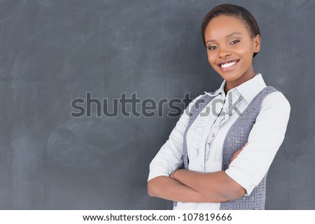 Teacher smiling with arms crossed in a classroom - stock photo