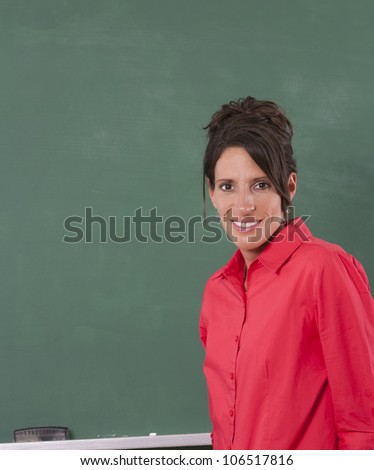 Teacher standing in front of chalkboard of classroom