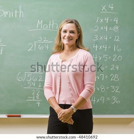Teacher standing near blackboard - stock photo