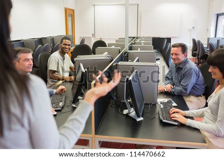 Teacher talking to group in computer room in college - stock photo