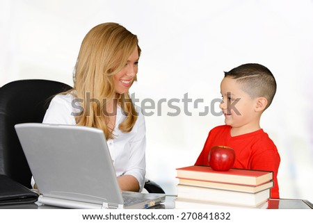 Teacher talking to her pupil about schoolwork - stock photo