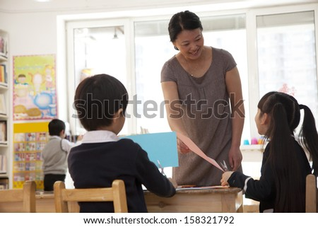Teacher talking to students doing art in classroom