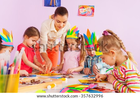Teacher teach preschool kids in art class - stock photo