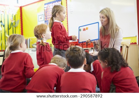 Teacher Teaching Spelling To Elementary School Pupils - stock photo