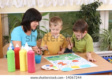teacher two preschoolers and colorful painting - education