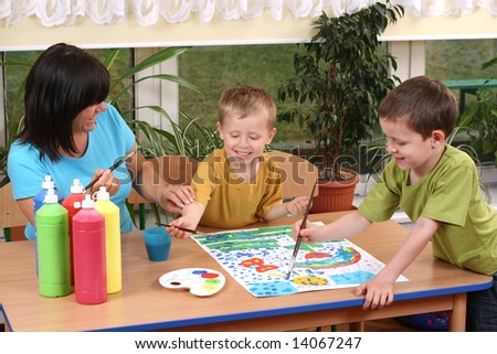 teacher two preschoolers and colorful painting - education - stock photo