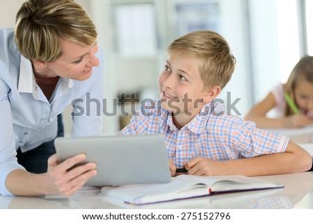 Teacher using digital tablet as educational tool in class - stock photo