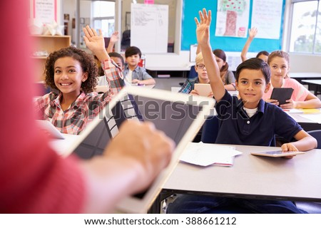 Teacher using tablet computer in elementary school lesson - stock photo