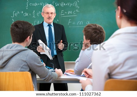 Teacher with a group of high school students in classroom