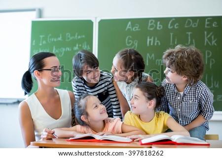 Teacher with children in classroom - stock photo
