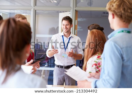 Teacher With College Students Standing By Desks In Classroom - stock photo