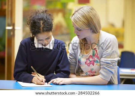 Teacher With Female Pupil Reading At Desk In Classroom - stock photo