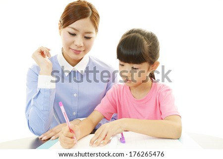 Teacher with girl studying - stock photo