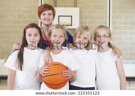 Teacher With Girls School Basketball Team - stock photo