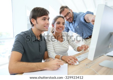 Teacher with group of students in class working on desktop - stock photo