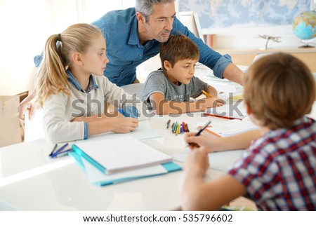 Teacher with kids in class giving writing lesson