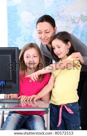 Teacher with kids in front of desktop computer - stock photo