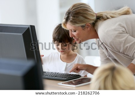 Teacher with little girl in class using computer and tablet - stock photo