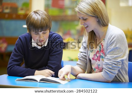 Teacher With Male Pupil Reading At Desk In Classroom