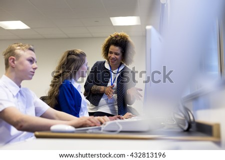 Teacher with student in a computer lesson. She is explaining something on the students computer. - stock photo