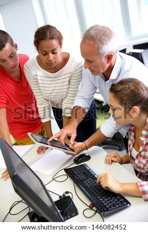 Teacher with students in computing class - stock photo