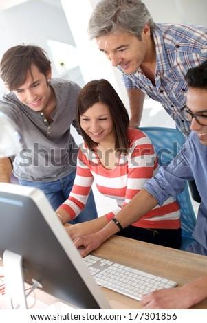 Teacher with students working on desktop  - stock photo