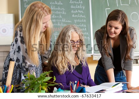 Teacher with two of her students checking something behind her desk - stock photo